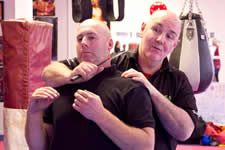 Sam Markey level 4 chief self defence instructor KAPAP UK demonstrating a behind the back with knife to throat disarm